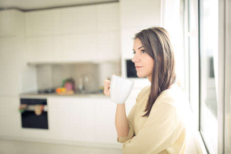 Woman enjoying,holding cup of hot beverage,coffee or tea.Enjoying her morning coffee in the kitchen.Savoring a cup of coffee in bliss and appreciation.Emotional.Thinking