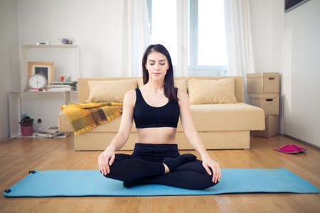 Carefree calm woman meditating.Healthy living.Enjoying peace and serenity.Beautiful fit female fitness woman practicing yoga in home.Living room for after work relaxation and exercise.Lotus pose