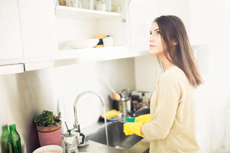 Hand cleaning.Young housewife woman washing dishes in kitchen.Cleaning and washing dishes and pans with yellow rubber gloves.Cleaning kitchen.Tiring and boring manual housework.Housekeeping.Chores Standard-Bild