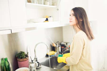 Hand cleaning.Young Hausfrau Frau Abwasch in kitchen.Cleaning und Abwaschen und Pfannen mit gelben Gummi gloves.Cleaning kitchen.Tiring und langweilige manuelle housework.Housekeeping.Chores Standard-Bild - 52646801