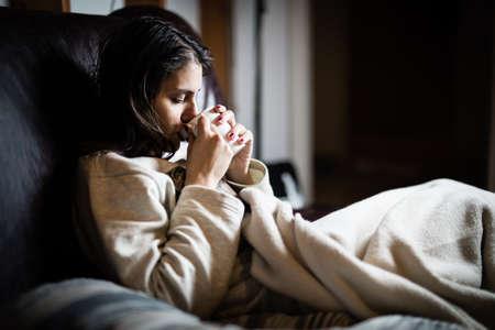 Kranke Frau im Bett, krank, Tag abzublasen von work.Drinking Kräuter tea.Vitamins und heißen Tee für flu.Woman Gefangen Cold.Virus. Dysentery.Diarrhea.Woman suchen krank und müde Standard-Bild - 52646802