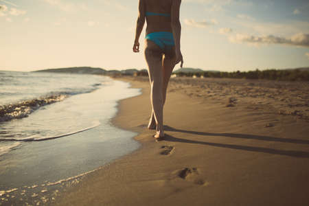 Best beach vacation destination.Beautiful sunset sand beach getaway.Woman walking sand beach.Summer beach woman enjoying summer and sun.Freedom, happiness.Fit and healthy summer body.Footsteps in sand