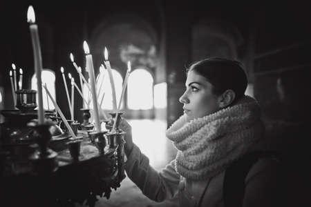 Junge weibliche Anzünden von Kerzen in einer Kirche während praying.Yellow Votivkerzen burning.Woman in St. Alexander-Newski-Cathedral.Christianity.Strong christliche Religion fait zu Gott zu beten Standard-Bild - 52646809