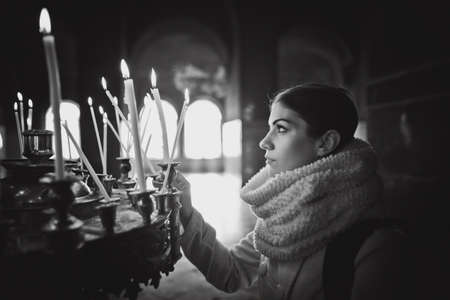 Young female lighting candles in a church during praying.Yellow votive candles burning.Woman praying to god at St. Alexander Nevsky Cathedral.Christianity.Strong christian religion fait Zdjęcie Seryjne