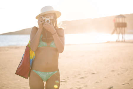 camera girl: Attractive fit trendy modern hipster woman taking photos with retro vintage film camera.Lifestyle photographer.Summer beach woman taking picture during summer holiday vacation travel.Sexy cool hipster