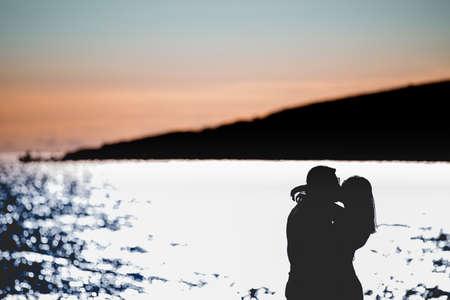 Silhouette eines Paares in der Liebe am Strand von sunset.Love story.Man und einer Frau auf dem beach.Beautiful Paar in den sunlight.Silhouettes küssen gegen den sun.Summer love.Passion.Honeymoon Standard-Bild - 52646814