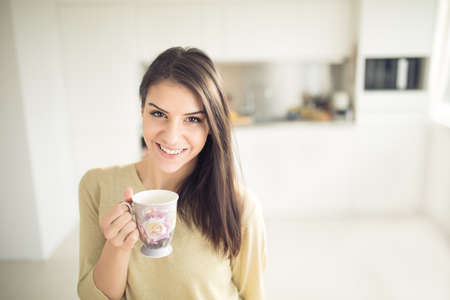 Modern working woman lifestyle-drinking coffee or tea in the morning in the kitchen,starting your day.Positive energy and emotion.Productivity,happiness,enjoyment,determination concept.Morning ritual