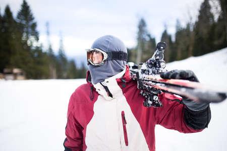 Junger Mann hält ski.Skier Ski Blick auf die mountains.Side von stattlicher Skifahrer Mann mit Maske und hält Ski-Ausrüstung, die Spaß auf den Bergen, aktiven Winterurlaub hält Konzept Standard-Bild - 52647709
