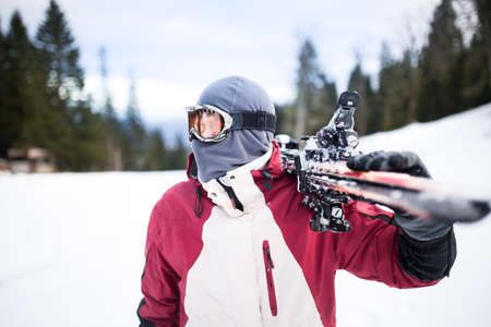 Young man holding ski.Skier holding skis looking at the mountains.Side view of handsome skier man with mask and holding ski equipment,having fun on the mountains,active winter vacation concept