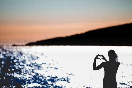 Freie glückliche Frau genießen sunset..Embracing den goldenen Sonnenschein Abendrot, genießen Ruhe, Gelassenheit in nature.Vacation Vitalität gesund leben concept.Silhouette Hand in Herzform Standard-Bild - 52647708
