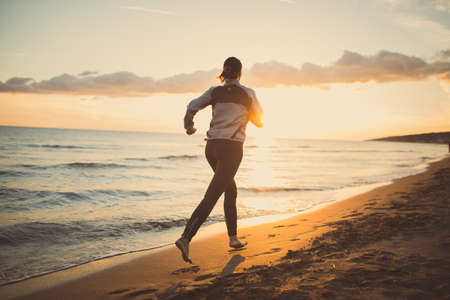 Runner woman jogging on beach in sports bra top.Beautiful fit female fitness woman training and working out outside in summer as part of healthy lifestyle.Fitness woman running at sunset on beach Zdjęcie Seryjne