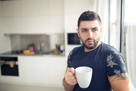 Man holding cup of hot beverage,coffee or tea.Enjoying his morning coffee in the kitchen.Looking trough the window.Thinking.Worried pensive man stress relief.Modern entrepreneur.New day starting.Ideas Stock Photo