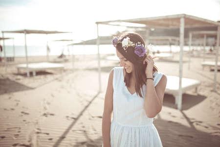 Sommer-Strand-Mode Frau genießen Sommer und Sonne, den Strand in der Nähe von klaren, blauen Meer gehen, lächelnd. Konzept der Sommergefühl, Freiheit, Glück. Fit und gesund Sommer Körper Blumenhut Standard-Bild - 52647710