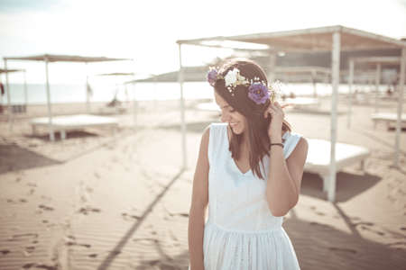 Summer beach fashion woman enjoying summer and sun, walking the beach near clear blue sea, smiling. Concept of summer feeling, freedom, happiness. Fit and healthy summer body flower hat