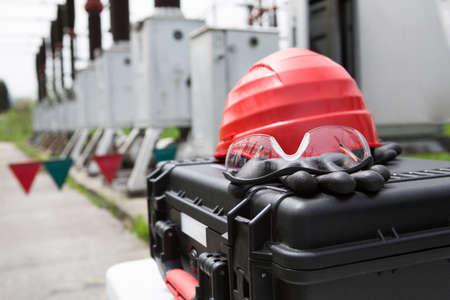Schutzhelm, Schutzbrille und Handschuhe auf Werkzeug box.Safety Rädersatz close up, Sicherheitsausrüstung für die Arbeit im Freien bei Hochspannungs-Strom Umspannwerk, Strom plant.Safety für Elektriker bei der Arbeit Standard-Bild - 52647719