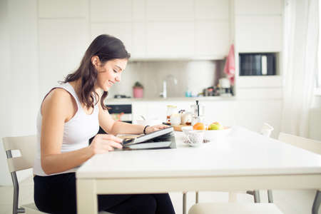 Young brunette is reading the newspaper while having breakfast at home.Modern woman lifestyle-healthy fitness breakfast,coffee and fruit,reading motivational quotes.Starting your day,positive energy Standard-Bild