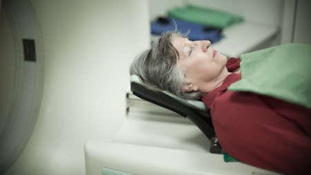 Alte Dame schlafen auf einem CT-Scan Bett und Panel-Steuerung von Radiologischer technician.Patient Bereiten Sie sich für Computerized Axial Tomography CAT Scan.Examining ältere Frau mit CT scan.Computerised Tomographie. Standard-Bild - 52647721