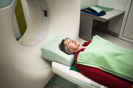 Modern medical equipment, preventional medicine and healthcare.Computer tomography scan.Old woman patient at computerized axial tomography CAT scan.Examining cancer patient with CT.Tumor detection Stock Photo
