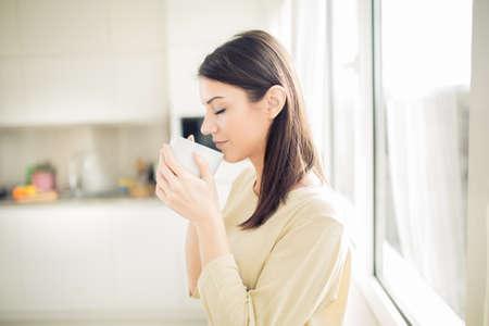capuchino: Mujer joven que disfruta, sosteniendo la taza de bebida caliente, café o té en la mañana sunlight.Enjoying su café de la mañana en el kitchen.Savoring una taza de café de la respiración en el aroma en la felicidad y la apreciación Foto de archivo