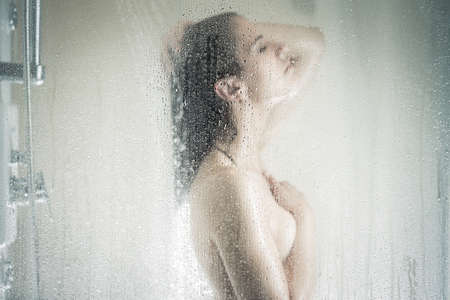 female sex: Relief and relaxation after long stressful day. Taking moment for yourself concept. Skincare, spa and aromatherapy. Unfocused portrait of a woman showering through the bath screen with little drops