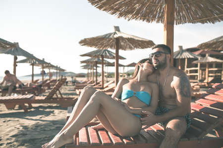 Happy romantic couple enjoying beautiful sunny day at the beach.Couple in hug relaxing on chaise-lounges.Young and fit couple on holiday enjoying in the shade of parasol.Kissing.Summer love date.