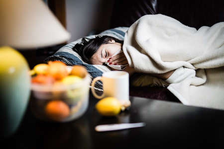 sick day: Sick woman in bed,calling in sick,day off from work.Thermometer to check temperature for fever.Vitamins and hot tea in front.Flu.Woman Caught Cold.Virus.Sick woman laying in bed under wool blanket Stock Photo