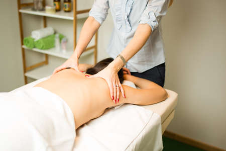 Skin and body care.Young woman getting spa treatment at beauty salon.Female enjoying relaxing back massage in cosmetology spa center.Woman lying and relaxing.Physiotherapy after spine injury.Neck pain Stock Photo