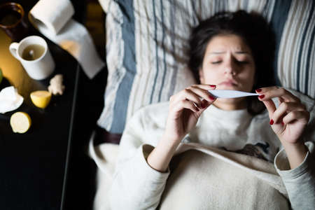 Mujer joven enferma en la cama en su casa con la gripe, la medición de temperature.Thermometer para comprobar la temperatura de la mujer que pone en fever.Flu.Virus.Sick bed.Focus en el termómetro