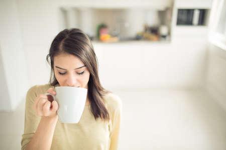 respiracion: Mujer joven que disfruta, sosteniendo la taza de bebida caliente, café o té en la mañana sunlight.Enjoying su café de la mañana en el kitchen.Savoring una taza de café de la respiración en el aroma en la felicidad y la apreciación Foto de archivo