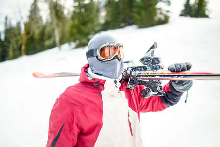 Young man holding ski at ski resort.Skier holding skis looking at the mountains.Side view of handsome skier man with mask and holding ski equipment,active winter vacation concept. Stock Photo