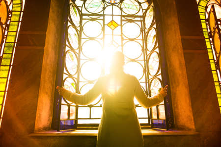 Religious christian woman looking trough the stained glass church window light.Woman praying to god at St. Alexander Nevsky Cathedral.Finding serenity in religion,faith and hope concept.Enlightenment