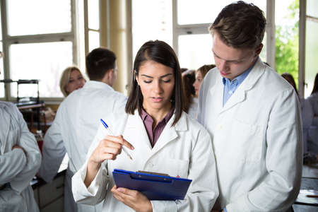 Scientific researcher holding a folder of chemical experiment research. University coworkers,Pharmacy,Medicine.Working in teams for a better result.Science project team work. Stock Photo