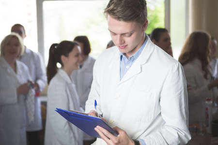 Scientific male researcher holding folder of chemical experiment research.Science students working with chemicals in the lab at the university.Happy student, content for experimental results.Pharmacy Stock Photo