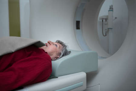 Old lady sleep on a CT Scan bed and panel control by Radiologic technician.Patient Prepare For Computerized Axial Tomography CAT Scan.Examining older woman with CT scan.Computerised tomography.
