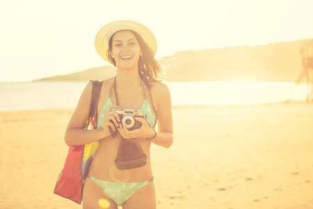 Attractive fit trendy modern hipster woman taking photos with retro vintage film camera.Lifestyle photographer.Summer beach woman taking picture during summer holiday vacation travel.Sexy cool hipster