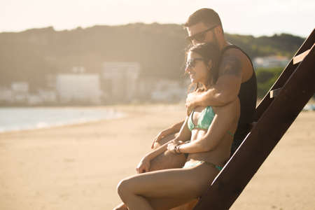 anniversary beach: Romantic couple in hug watching sunrise sunset together.Young man and woman in love hugging and enjoying day at the beach.Flirting on summer vacation.Watching horizon,waves.Romance.Young love.Date