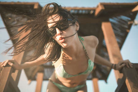 Beach woman having fun in summer vacation holidays.Lifestyle summer portrait,relaxed standing on the lifeguard tower.Happy woman dancing on the beach.DJ on the beach party