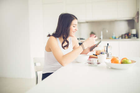 Young brunette is reading the newspaper while having breakfast at home.Modern woman lifestyle-healthy fitness breakfast,coffee and fruit,reading motivational quotes.Starting your day,positive energy Stockfoto