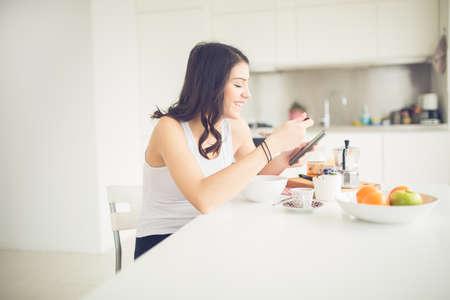 saludable: Morena joven está leyendo el periódico mientras toma el desayuno en el desayuno home.Modern aptitud de la mujer del estilo de vida saludable, café y fruta, la lectura de motivación quotes.Starting su día, la energía positiva Foto de archivo