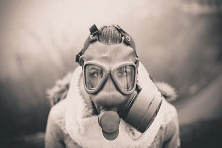 chemical hazard: Environmental disaster.Woman breathing trough gas mask,health in danger.Concept of pollution,apocalypse.Polluted air,environmental problems.Riot with gas mask.Smog,poisonous particles,bio hazard