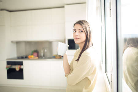 Woman enjoying,holding cup of hot beverage,coffee or tea.Enjoying her morning coffee in the kitchen.Savoring a cup of coffee in bliss and appreciation.Looking trough the window.Emotional.Thinking