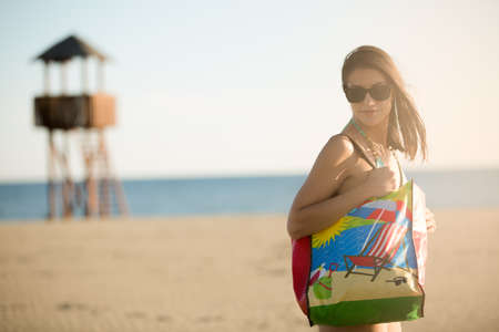 Attractive brunette woman with sunglasses carrying funny cartoon summer bag on the beach.Beach accessory.Going to the sandy beach vacation.Summer beach fashion style starter kit.Seaside off season.