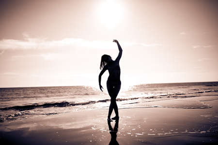 Carefree woman dancing in the sunset on the beach.Vacation vitality healthy living concept.Free woman enjoying sunset.Woman in embracing the golden sunshine of sunset,enjoying peace,serenity in nature
