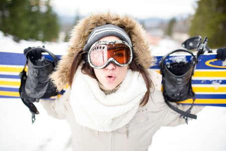 Snowboarding.Young schöne Frau mit Ski-Maske auf ihren Schultern und smiling.Concept von Winterferien ihr Snowboard auf den Skipisten Junge Frau im Skigebiet hält Snowboard halten Standard-Bild - 52489828