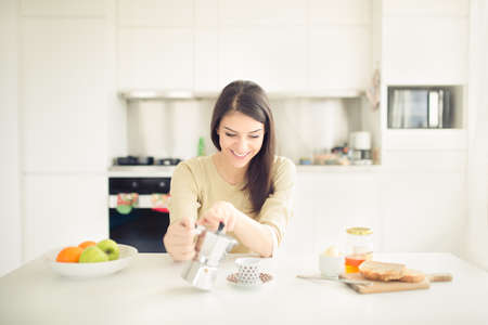 Modern working woman lifestyle-drinking moka coffee in the morning in the kitchen,starting your day.Positive energy and emotion.Productivity,happiness,enjoyment,determination.Morning ritual