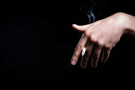 Cigarette nicotine addiction.Smoking a fag,cigarette butt.Unhealthy,danger,bad narcotic habit.Health risk,cancer illness.Young man smoking tobacco cigarette.Hand holding a cigarette smoke.Vice