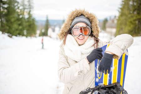 Schönes Mädchen im Winterwald mit Snowboard- und Sturmhaube Mädchen-Snowboarding in den Bergen auf Skisteigung Sportfrau in den schneebedeckten Bergen Junge Frau, die Snowboard hält Konzept von Winterferien Standard-Bild - 52489836
