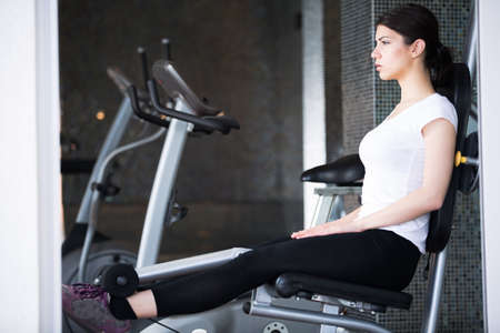 Young woman doing exercises in the gym.Gym fitness health club with young woman training with weights.. Young woman making an effort and training hard for hot fit body Standard-Bild