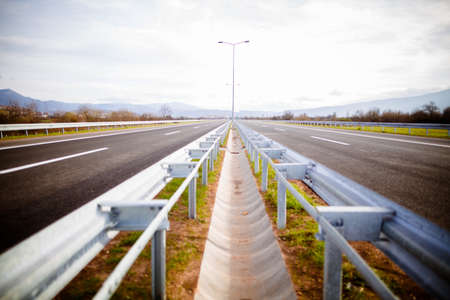 Freeway on a sunny day trough scenic green meadows.Motorway traveling long distance.Asphalt highways road in rural scene use land transport and traveling concept.Vehicular traffic.Fence.Highway bumper Stock Photo