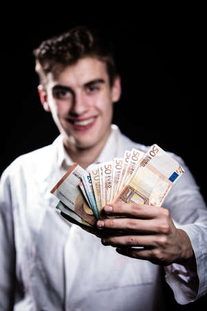 doctor giving dollars: Male medicine cheerful doctor holding in hands euro banknotes.Medic salary, prestige and high paid job, education, public health business, medical insurance concept.Bribe and corruption concept Stock Photo